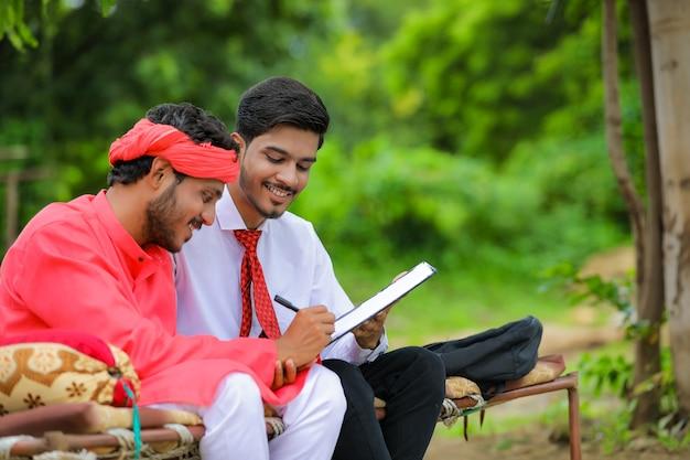 若いインドの農民が自宅の銀行家と文書にサインオン