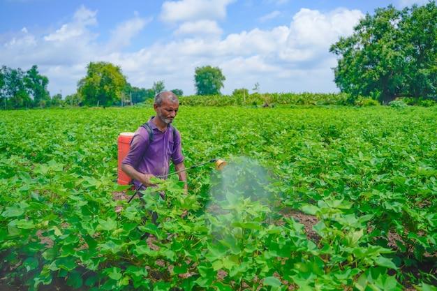 フィールドでスプレーしている若いインドの農夫