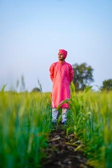 緑の麦畑に立っている若いインドの農夫