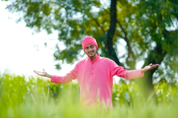麦畑に立って幸せな表情をしている若いインドの農夫