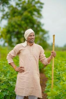 綿花農業分野に立っている若いインドの農民。