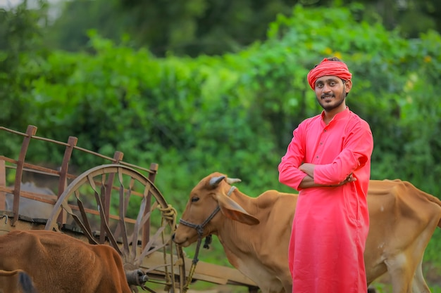Young indian farmer standing with farm cattle animal