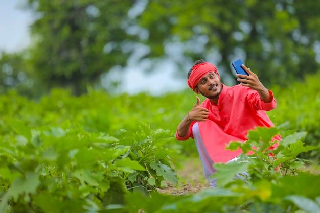 緑のナス畑でスマートフォンで自分撮りをしている若いインドの農夫