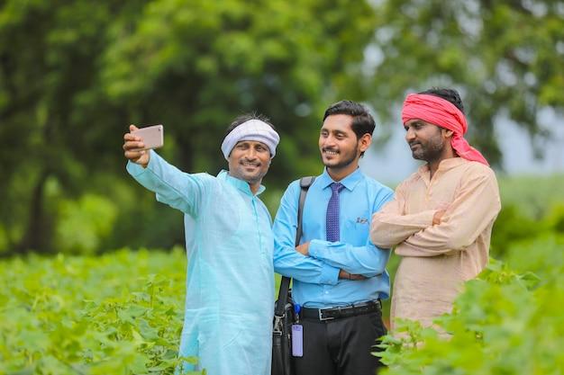 농업 분야에서 농업 경제학자 또는 은행가와 셀카를 찍는 젊은 인도 농부.