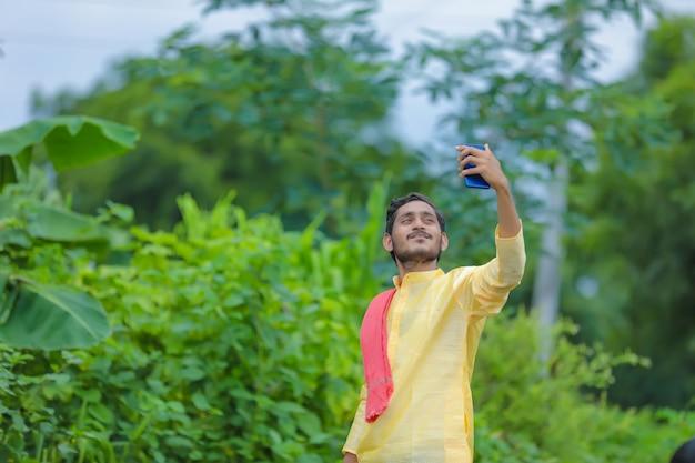 그의 스마트 폰으로 selfie를 복용하는 젊은 인도 농부