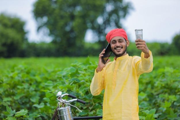 携帯電話で話し、綿花畑でお金を見せている若いインドの農民