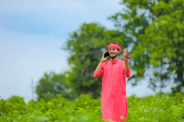 Молодой индийский фермер разговаривает по мобильному телефону на зеленом поле баклажанов