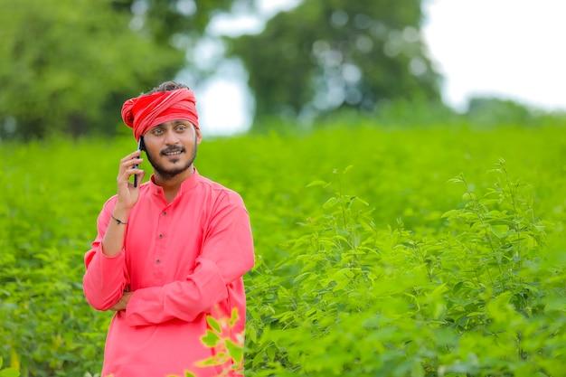 フィールドで携帯電話で話している若いインドの農夫