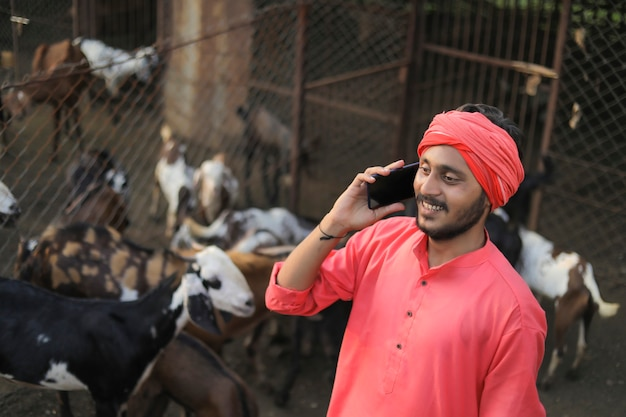 ヤギの酪農場でスマートフォンで話している若いインドの農民