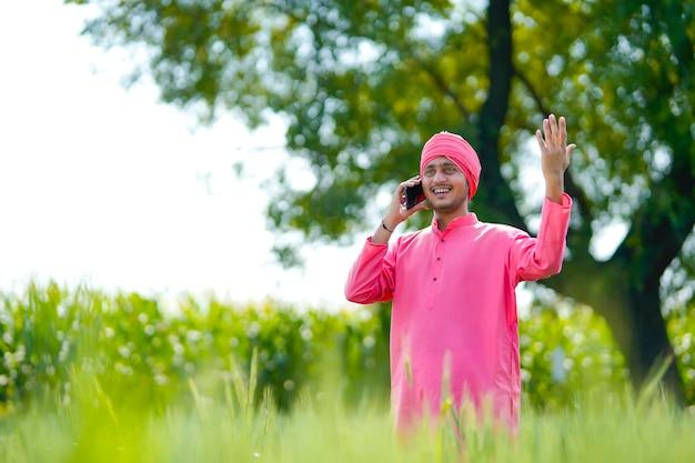農業分野でスマートフォンで話している若いインドの農民