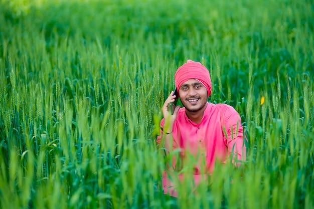 小麦畑でスマートフォンで話している若いインドの農民