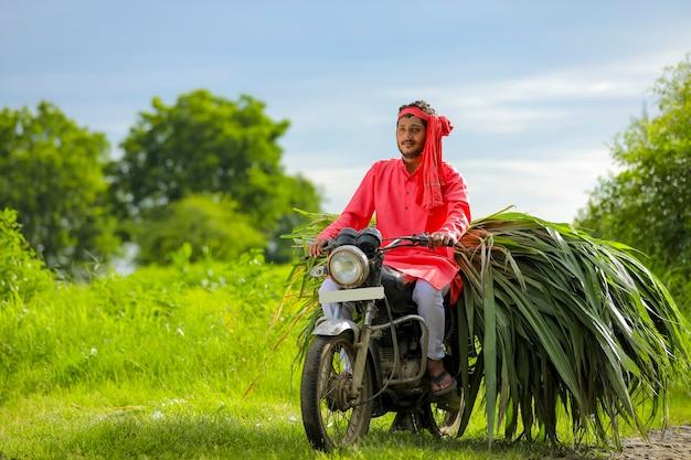 牛の餌を運ぶ若いインドの農民