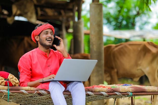ノートパソコンを使用している若いインドの農民
