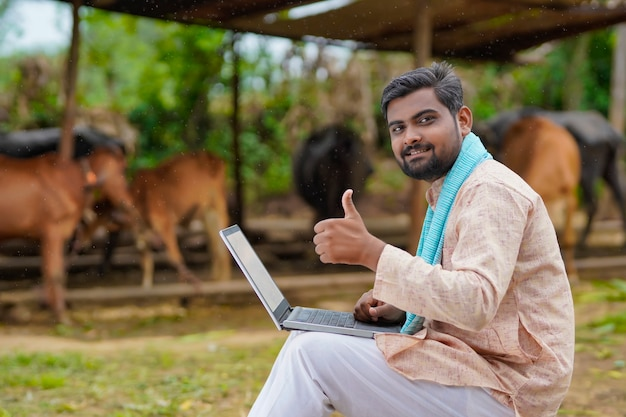 Young indian farmer using laptop at his cattle farm