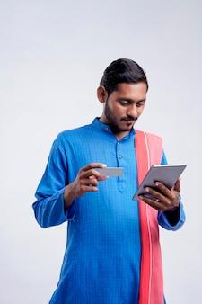 흰색 바탕에 스마트폰과 은행 카드를 사용하는 젊은 인도 농부.