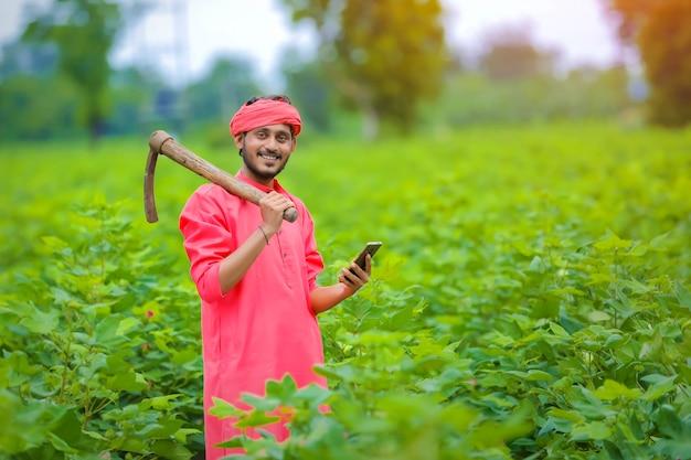 緑の綿花畑でスマートフォンを使用して若いインドの農民