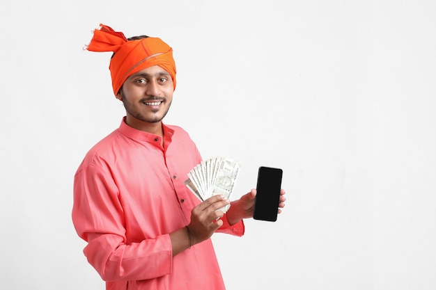 Young indian farmer using smartphone and showing money on white background.
