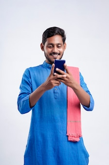 Young indian farmer using smartphone on white background.