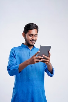 Young indian farmer using tablet and giving expression on white background.