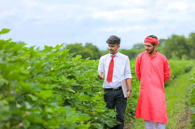 フィールドに銀行家を持つ若いインドの農夫