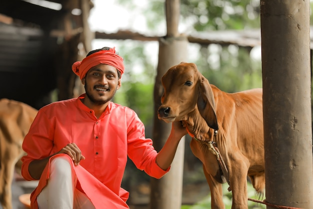 Молодой индийский фермер с козой в сельской местности