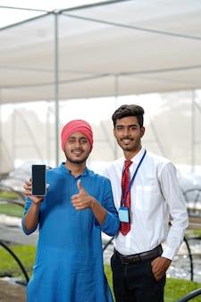 ポリハウスや温室でスマートフォンを見せている農学者と若いインドの農民