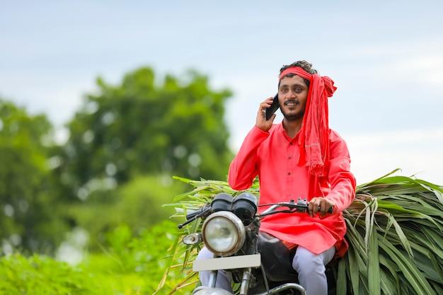 バイクで牛の餌を持っている若いインドの農夫