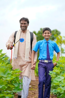 녹색 농업 분야에서 그의 아들과 함께 젊은 인도 농부.
