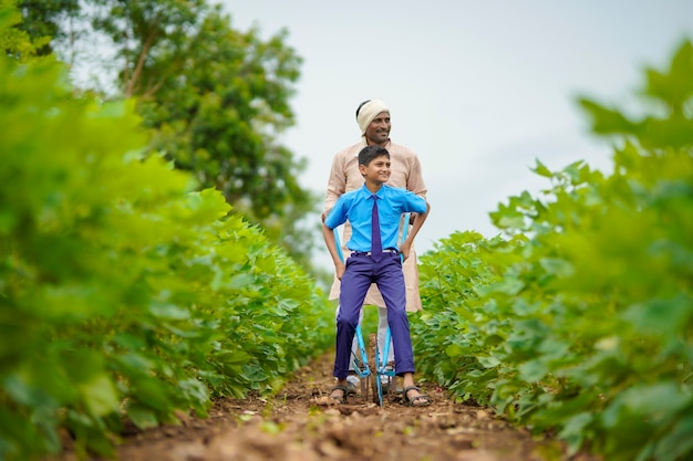 Young indian farmer with his son at green agriculture field.