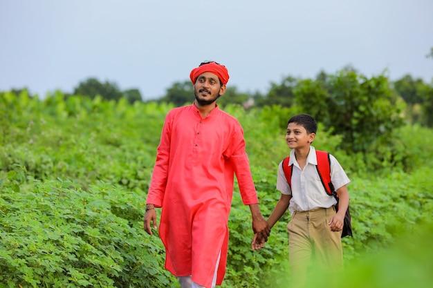 フィールドに彼の息子と若いインドの農夫