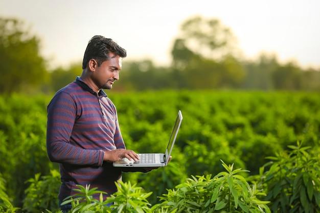 Молодой индийский фермер с ноутбуком