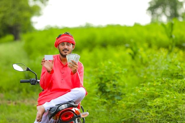 お金とクレジットカードを持つ若いインドの農民