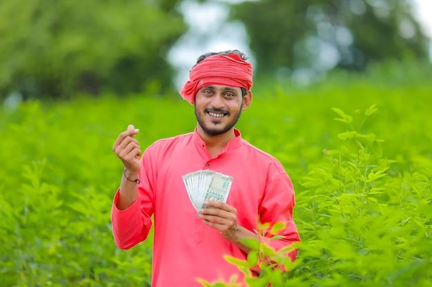 Молодой индийский фермер с деньгами на поле