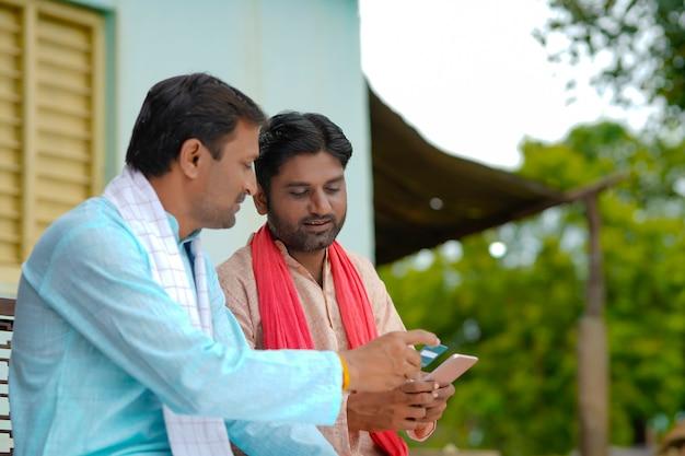 自宅でスマートフォンでデビットカードまたはクレジットカードを使用している若いインドの農家