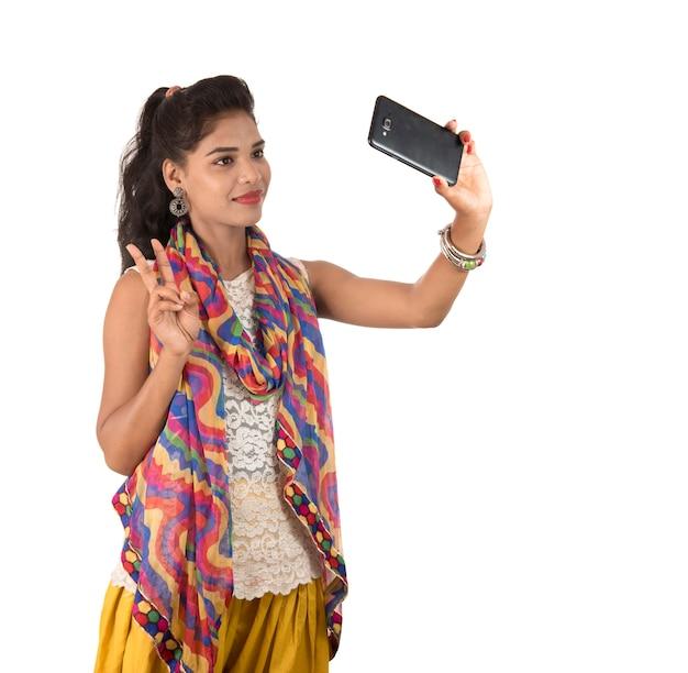 Молодая индийская девушка с помощью мобильного телефона или смартфона, изолированные на белом фоне