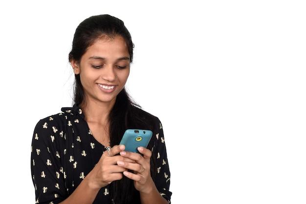白い背景で隔離の携帯電話やスマートフォンを使用して若いインドの女の子