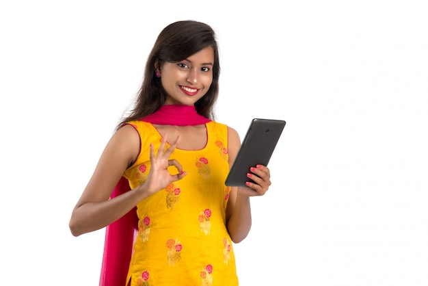 Молодая индийская девушка с помощью мобильного телефона или смартфона, изолированного на белом пространстве