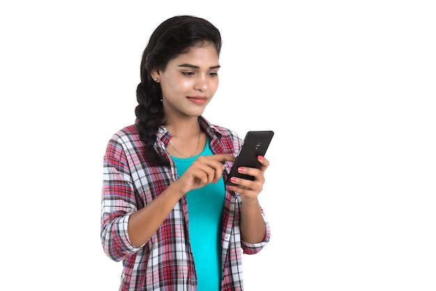 白い壁に隔離された携帯電話やスマートフォンを使用して若いインドの女の子