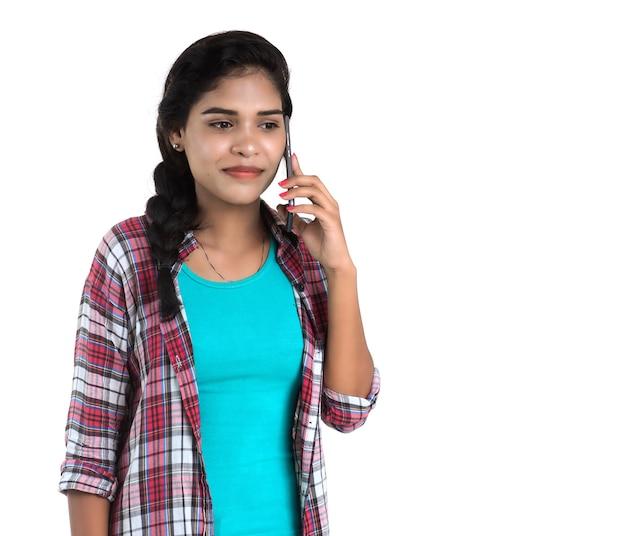 孤立した携帯電話やスマートフォンを使用して若いインドの女の子