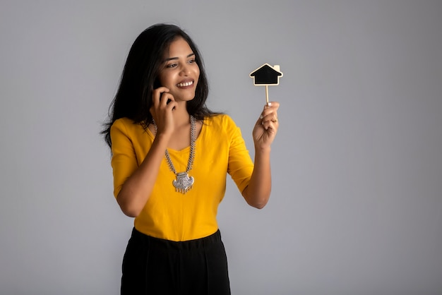 Молодая индийская девушка с помощью мобильного телефона или смартфона и показывает небольшую доску на сером.