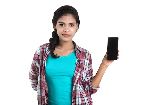 Young indian girl using a mobile phone or smartphone isolated