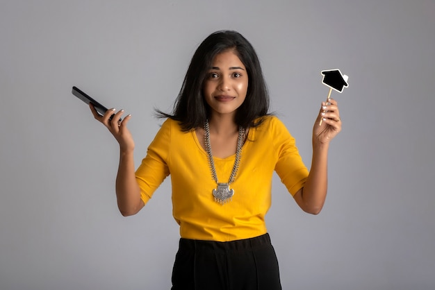 Young indian girl using mobile phone or smartphone and showing small board on gray.