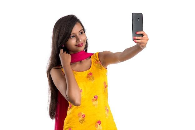 Young indian girl using a tablet, mobile phone or smartphone isolated on a white