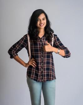 Молодая индийская девушка с рюкзаком показывает большой палец и позирует на серой стене