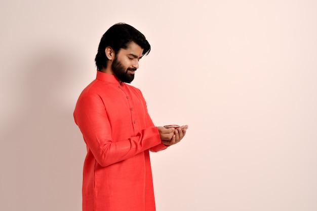 젊은 인도 가이가 디왈리를 위해 디야를 잡고 오렌지 쿠르타 측면 모습을 입고 있다