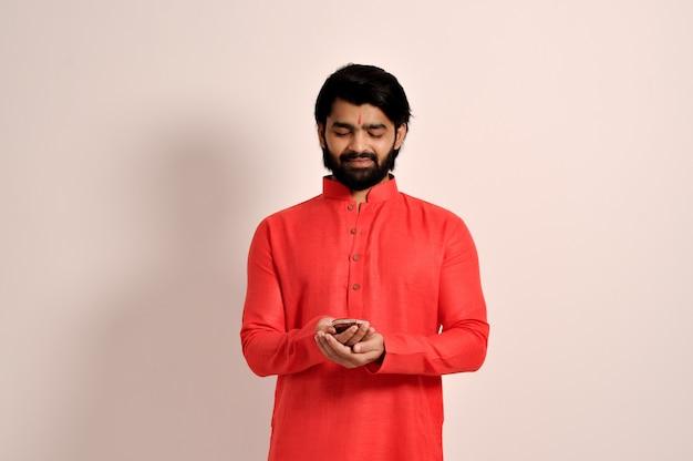 디왈리를 위해 디야를 잡고 오렌지 쿠르타를 입은 젊은 인도 남자