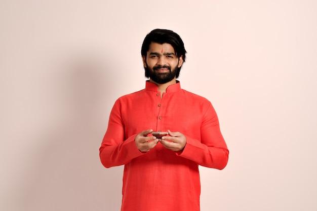 디왈리를 위해 디야를 들고 오렌지 쿠르타를 입은 젊은 인도 남자