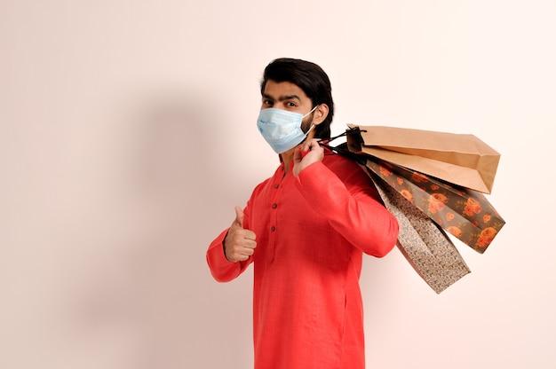 쿠르타 마스크를 쓰고 쇼핑백을 들고 엄지손가락을 치켜든 젊은 인도 남자