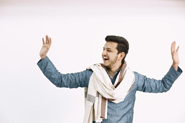 手を上げて若いインド人。孤立した白い壁で踊る。