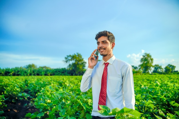 Young indian handsome agronomist talking on smartphone at field